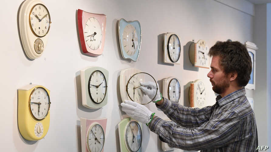 FILE - Master watchmaker Matthias Beck moves the hands of some vintage kitchen clocks at the German Clock Museum in Furtwangen, southern Germany, March 19, 2018.