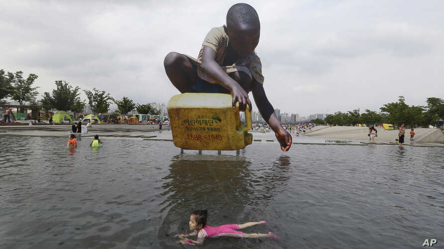 A girl swims to escape a heat in front of a large cutout that raises awareness on water shortage, at the Han River Park in Seoul, South Korea, Tuesday, Aug. 4, 2015. A heat wave warning was issued in Seoul as temperatures soared above 32 degrees Cels