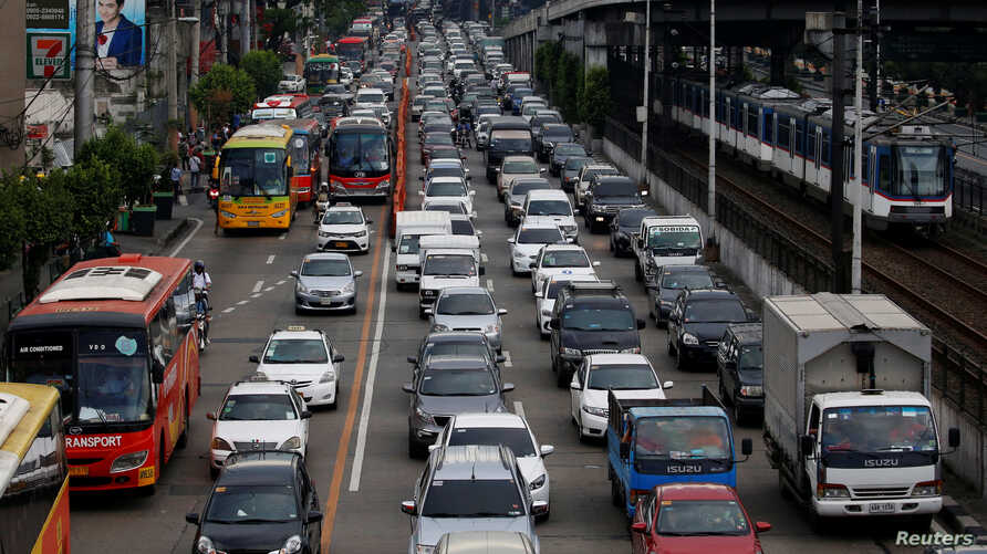 Motorists drive through a heavy traffic flow near a passing metro train along the main highway EDSA in Makati, Metro Manila, Philippines, June 21, 2016.