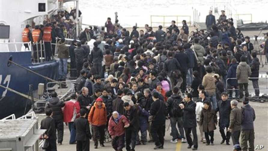 South Koreans surrounded by relatives and media as they arrive at port in Incheon, west of Seoul, South Korea, 24 Nov 2010