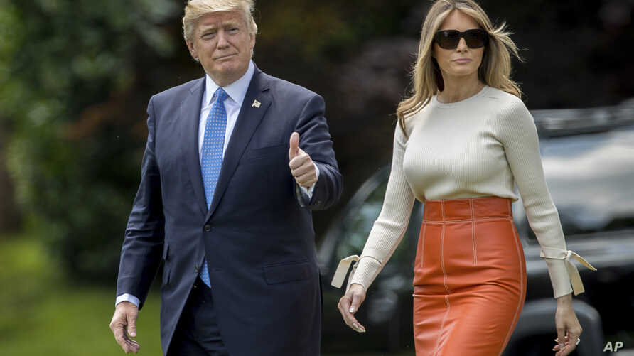 President Donald Trump, accompanied by first lady Melania Trump, gives a thumbs-up as they walk across the South Lawn of the White House in Washington, May 19, 2017.