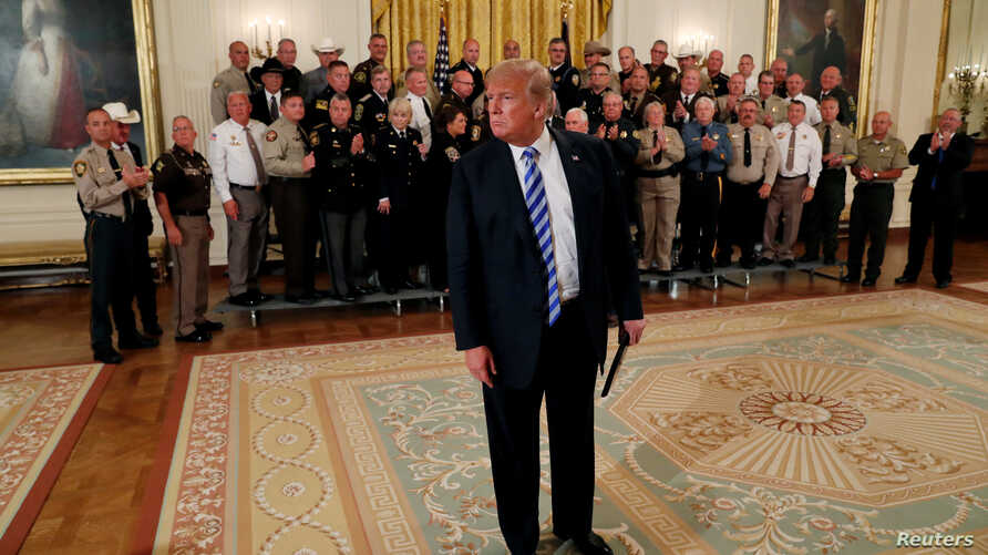 U.S. President Donald Trump approaches the news media to listen to a question about an anonymous op-ed from the New York Times after an event in the East Room at the White House in Washington, Sept. 5, 2018.