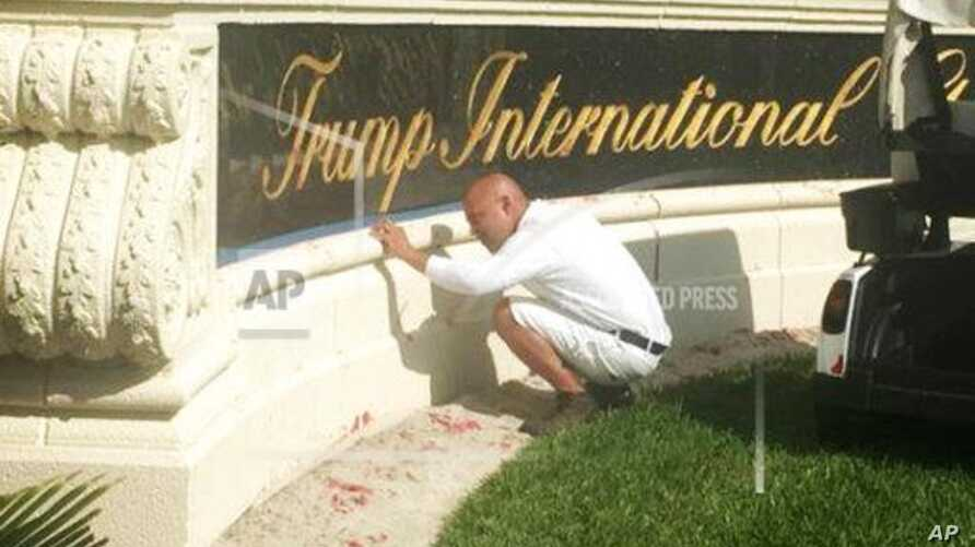 A worker cleans up red paint from the stone sign at the entrance to the Trump International Golf Club in West Palm Beach, Florida, April 1, 2018.