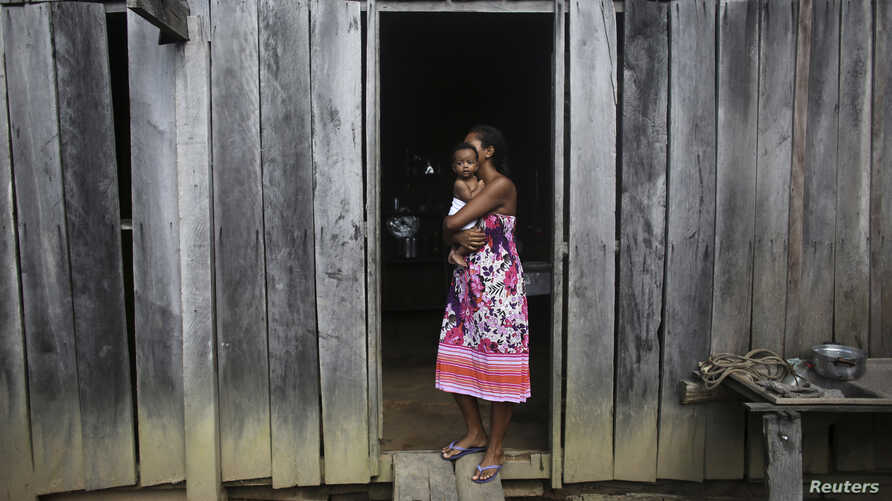 A woman holds her daughter outside their home in the Amazon rainforest near the city of Uruara, Para State, Brazil, April 20, 2013.