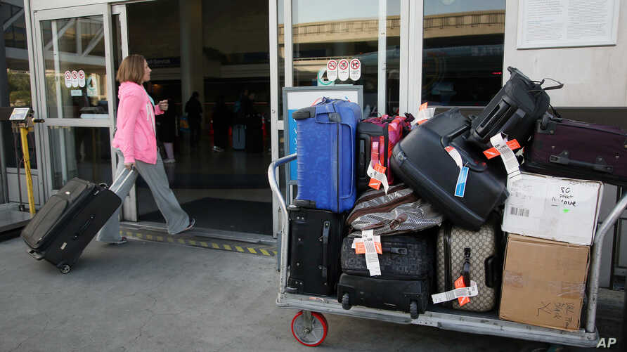 FILE - A baggage cart sits outside a terminal at Los Angeles International Airport in Los Angeles, March 27, 2014.