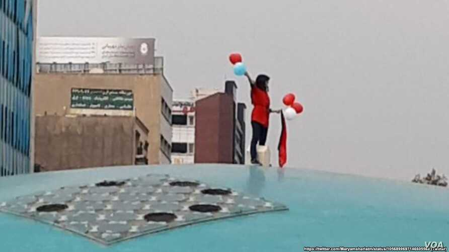 An image taken from social media shows a woman staging a public protest against Iran's strict dress code in Tehran on October 29.