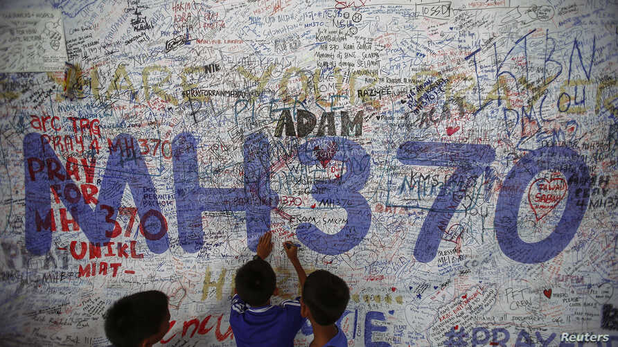 FILE - Children write messages of hope for passengers of missing Malaysia Airlines Flight MH370 at Kuala Lumpur International Airport June 14, 2014.