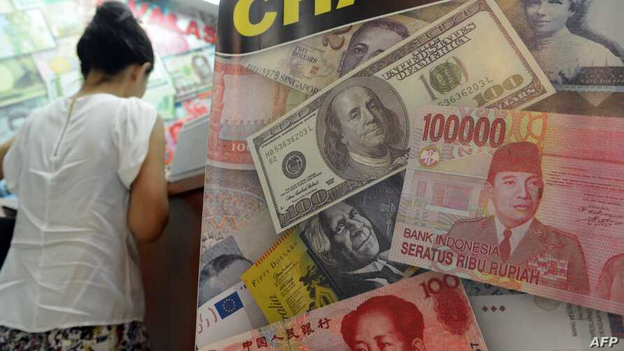 US dollar, Indonesian rupiah and Chinese renminbi currencies are displayed in the poster of a money exchange shop in Jakarta on June 12, 2013.