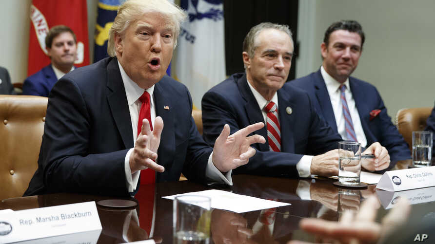 President Donald Trump speaks during a meeting with House Republicans in the Roosevelt Room of the White House in Washington, Feb. 16, 2017. From left are, Trump, Rep. Chris Collins, R-N.Y., and Rep. Duncan Hunter, R-Calif. Both Collins and Hunter ar