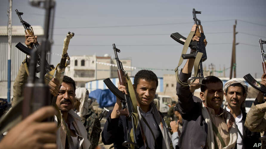 Houthi Shiite Yemeni hold their weapons during clashes in near the presidential palace in Sanaa, Yemen, Jan. 19, 2015.