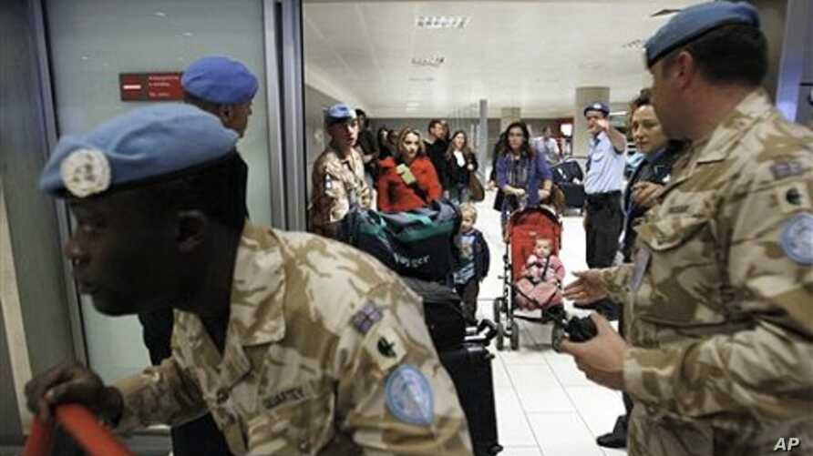 UN soldiers escort UN staff based in Egypt after they arrive in Cyprus' Larnaca airport, February 3, 2011.