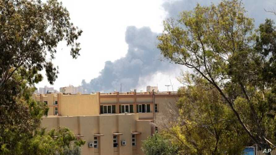 Smoke is seen after coalition air strikes in Tripoli, June 17, 2011