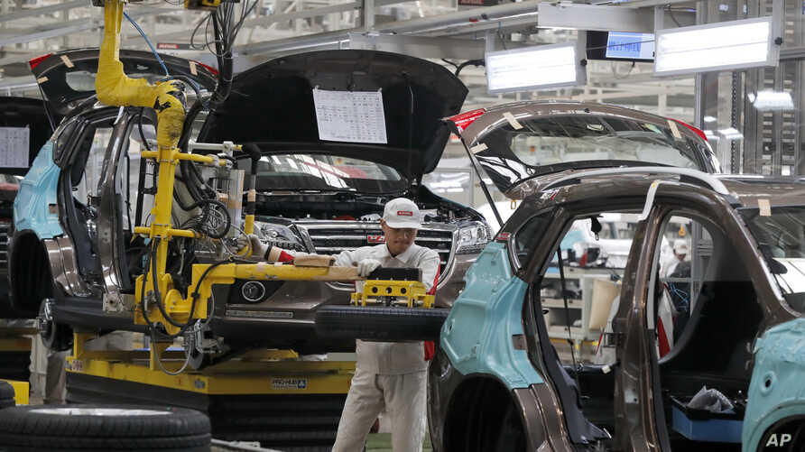 FILE - A worker prepares to put a spare tire into a Haval SUV H2 model in the Great Wall Motors assembly plant in Baoding in north China's Hebei province, Feb. 19, 2017.