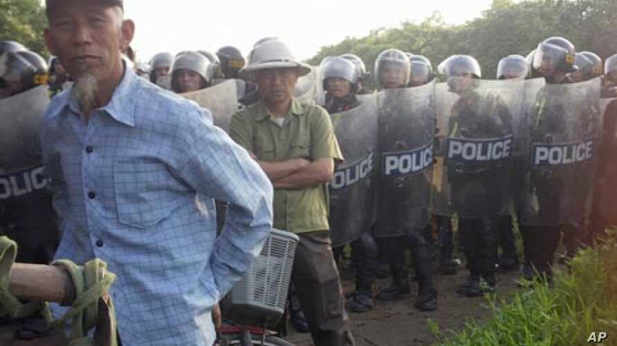 Villagers stand next to riot police deployed to Vietnam's northern Hung Yen province during a protest on April 24, 2012. Local residents tried block police from taking control of a disputed plot of land outside Hanoi in the second high-profile clash