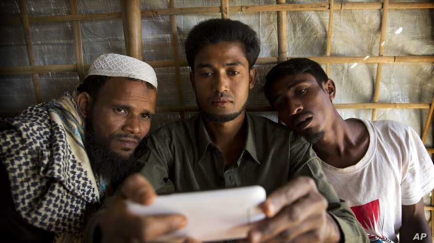 In this Jan. 14, 2018 photo, Rohingya Muslim refugee Mohammad Karim, 26, center, shows a mobile video of Gu Dar Pyin's massacre to other refugees in Kutupalong refugee camp, Bangladesh. On Sept. 9, a villager from Gu Dar Pyin, captured three videos o