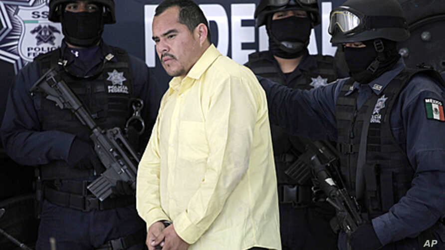 Federal police officers escort suspect Marco Antonio Guzman, aka 'El Brad Pitt,' an alleged member of the Mexican Juarez drug cartel, during a presentation to the press in Mexico City, Thursday, June 16, 2011