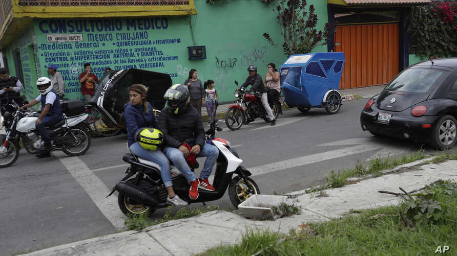Residents and motorcycle taxi drivers stop to look at marines blocking the area where a suspected drug gang leader and seven others were killed in a shootout in the Tlahuac district of Mexico City, July 20, 2017.