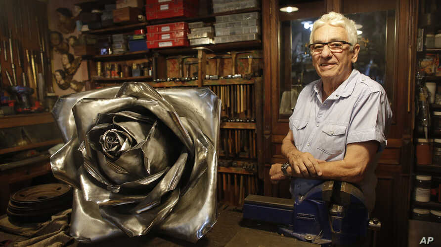 Juan Carlos Pallarols, 74, poses with a rose made with pieces of warplanes from the Falklands war, at his studio in Buenos Aires, Argentina, Jan. 25, 2017.