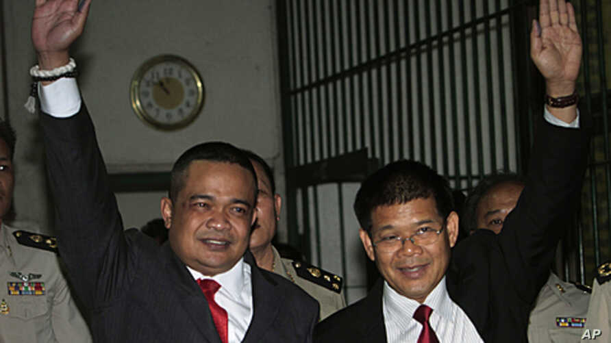 Red Shirt leaders Jatuporn Prompan, left, and Nisit Sinthuprai, raise their hands behind bars at the Criminal Court in Bangkok, May 12, 2011 as they are taken to the prison after their bails were revoked.