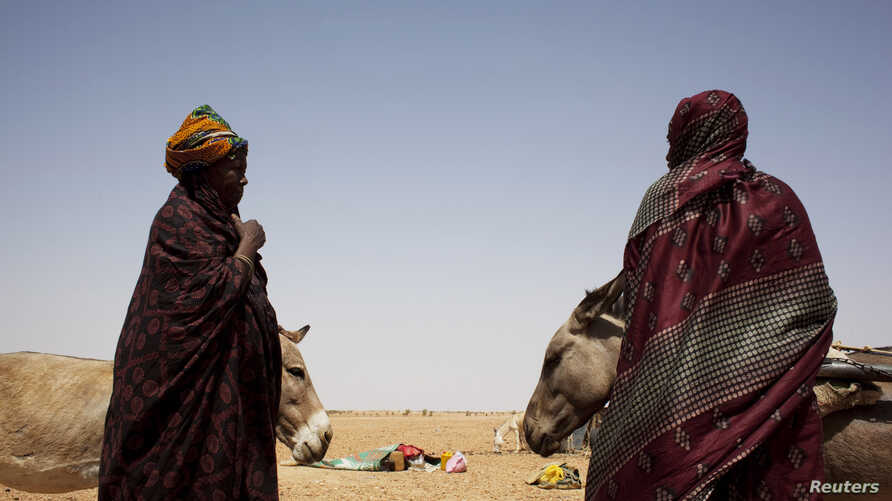 Women wait to load their carts with bags of rice and bottles of cooking oil at a food distribution center run by the Spanish NGO Accion contra el Hambre (Action against Hunger) in Tarenguel, Gorgol region, Mauritania, May 30, 2012.