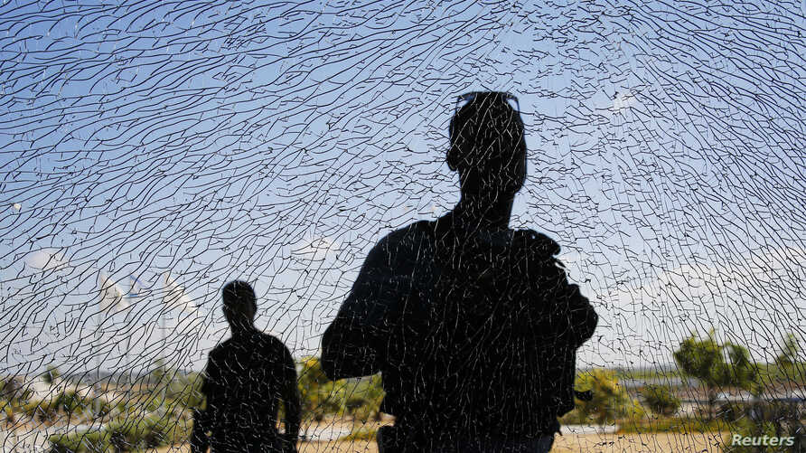 Israeli security personnel look at a window damaged by shrapnel after a short-range rocket landed on Tuesday near the Erez crossing July 16, 2014. An Israeli civilian was killed by the rocket fired from the Gaza Strip on Tuesday, the military said, t...