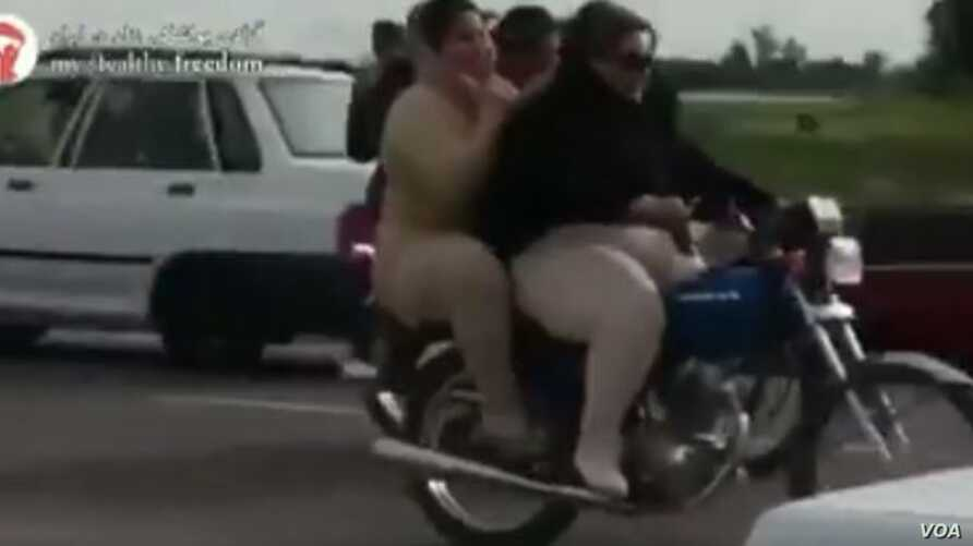 This image taken from video posted on Iranian investigative journalist Masih Alinejad's Facebook page shows two Iranian women riding a motorcycle.