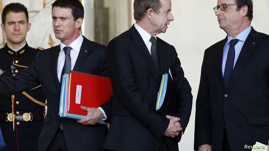 French President Francois Hollande (R) speaks with Justice Minister Jean-Jacques Urvoas (C) as Prime Minister Manuel Valls walks by following the weekly cabinet meeting at the Elysee Palace in Paris, Feb. 3, 2016.