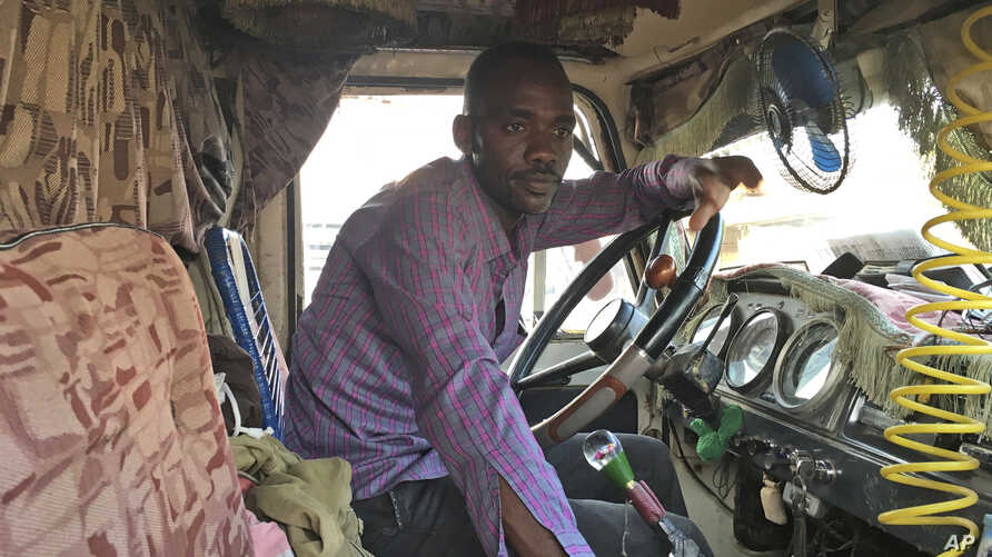 In this April 6, 2017, photo, Sudanese smuggler Sadiq Mohammed sits in his truck embarking on another cross-border journey.