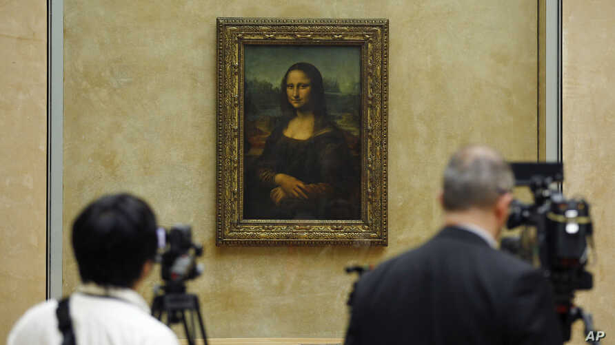 Members of the media are gathered next to the Mona Lisa, during an event to unveil the new lighting of Leonardo da Vinci's painting Mona Lisa earlier this year. The Mona Lisa is famous for her enigmatic smile.