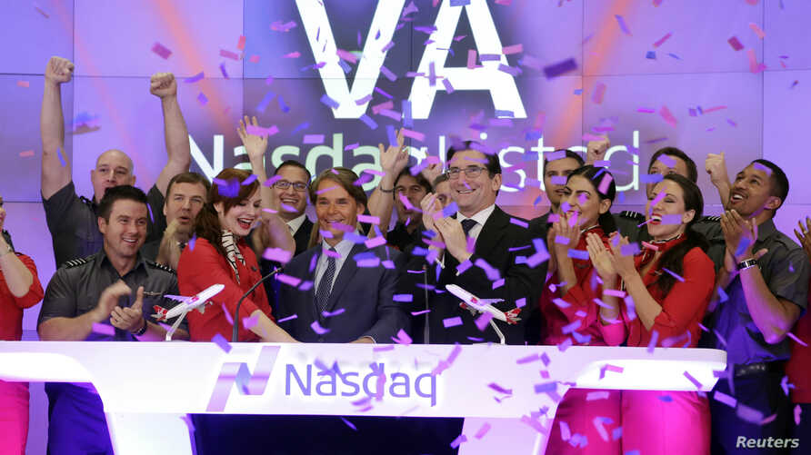 David Cush, third left front row, President & CEO of Virgin America is applauded and showered with confetti as he rings the opening bell at the Nasdaq MarketSite, to mark his company's IPO, in New York, Nov. 14, 2014.