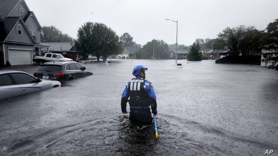 A member of the North Carolina Task Force urban search and rescue team wades through a flooded neighborhood looking for residents who stayed behind as Florence continues to dump heavy rain in Fayetteville, N.C., Sunday, Sept. 16, 2018.