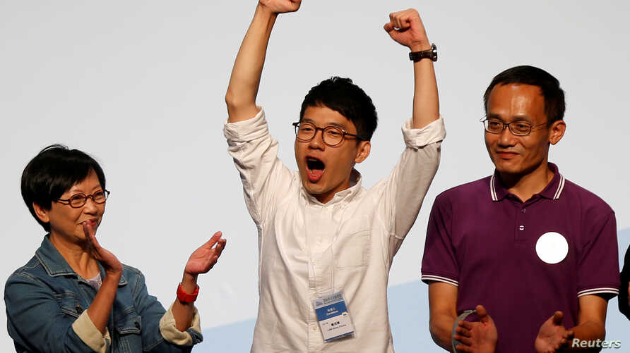 Student leader Nathan Law (C) celebrates on the podium after his win in the Legislative Council election in Hong Kong, China, Sept. 5, 2016.