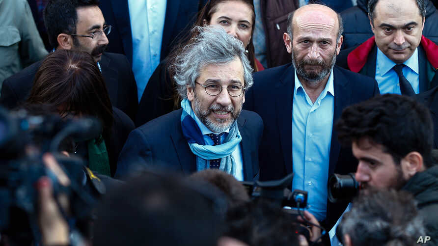 Can Dundar, the editor-in-chief of opposition newspaper Cumhuriyet, center-left, and Erdem Gul, the paper's Ankara representative, center-right, speak to the media before the start of their trial in Istanbul, April 1, 2016.