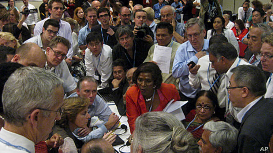 Ministers gather in a huddle where agreement was reached to extend the Kyoto Protocol during a plenary session at the United Nations Climate Change Conference (COP17) in Durban, December 11, 2011.