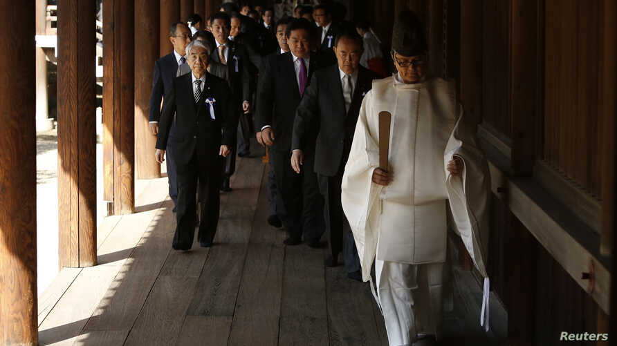 A group of lawmakers are led by a Shinto priest as they visit Yasukuni Shrine in Tokyo, April 22, 2014.