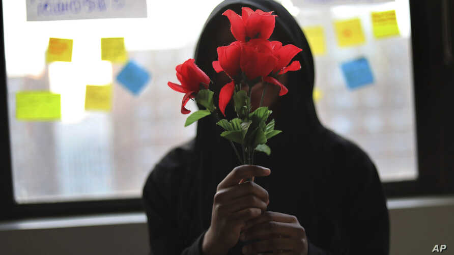 """A survivor of sexual assault holds plastic flowers after attending a meeting with the group """"Sisters in Strength"""" in the Brooklyn borough of New York, March 14, 2019."""