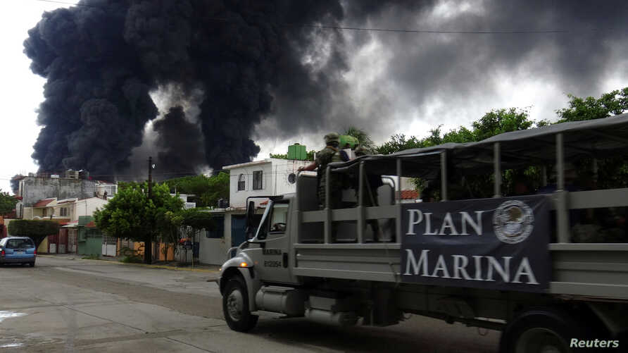 A truck of the Mexican Navy is seen as smoke from a fire at Mexico's state-owned oil firm Pemex Salina Cruz refinery billows in the background, in Salina Cruz, Oaxaca state, Mexico, June 14, 2017.