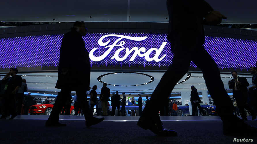 Attendees walk by the Ford display at the North American International Auto Show in Detroit, Jan. 11, 2016.