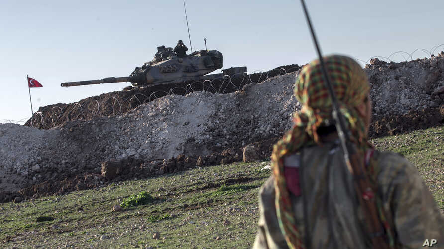 FILE - A Syrian Kurdish militia member of the YPG patrols near a Turkish army tank as Turks work to build a new Ottoman tomb in the background in Esme village in Aleppo province, Syria, February 22, 2015.
