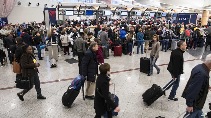 Passengers make their way past long lines at a ticket counter at Hartfield-Jackson Atlanta International Airport,  Dec. 18, 2017, in Atlanta.