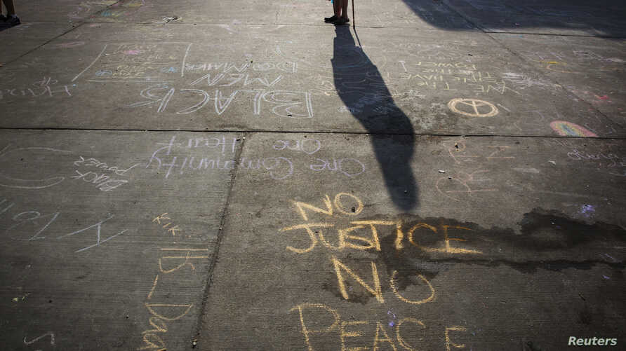 Messages written in a parking lot protest the shooting of Michael Brown in Ferguson, Missouri, Aug. 15, 2014.