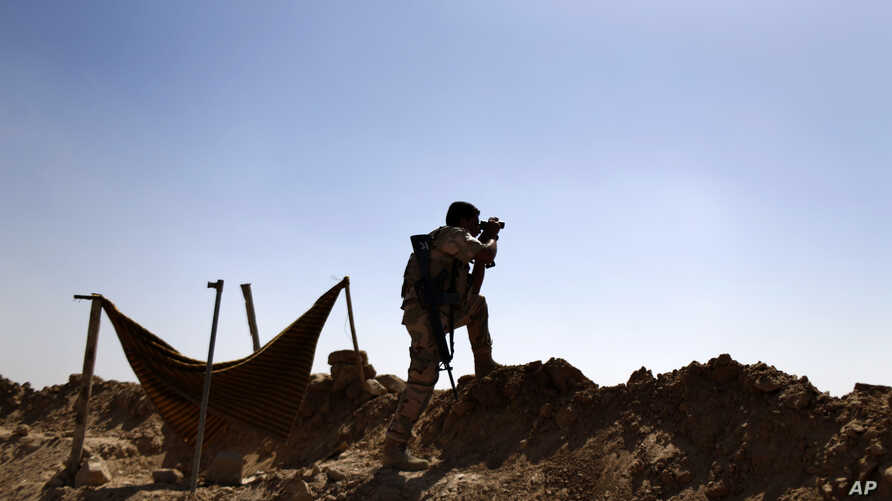 FILE - In this Sept. 26, 2014 file photo, a Kurdish Peshmerga fighter uses binoculars to check on Islamic State group's positions on the outskirts of Makhmour, 300 kilometers (186 miles) north of Baghdad, Iraq.
