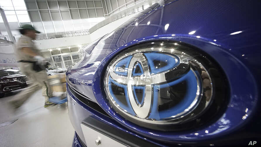 A worker walks past a Toyota car at a Toyota showroom in Tokyo, Wednesday, June 29, 2016.