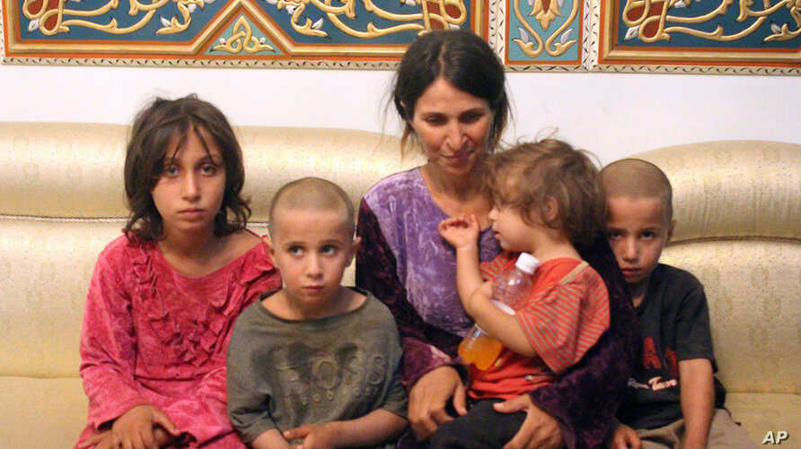 FILE - A photo, released by the Syrian official news agency SANA, shows Abeer Shalgheen and her four children after being freed by the so-called Islamic State group that kidnapped them on July 25 during a raid by the extremists on the southern provin