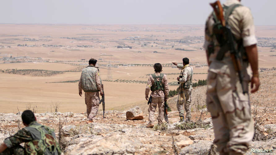 FILE - Fighters allied with Syria Democratic Forces (SDF) are seen near Manbij, northern Syria, June 1, 2016. Turkmen commander Hani al-Mulla was losely affiliated with the SDF.