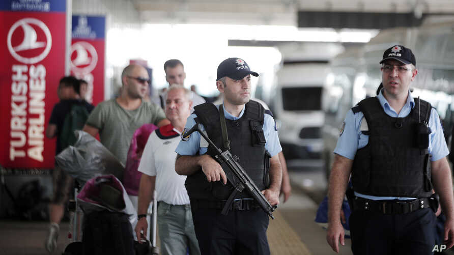 Turkish police officers patrol outside Istanbul's Ataturk airport, June 29, 2016. A day after suicide bombers killed scores of people at the airport, Turkey's prime minister has named the Islamic State group as the chief suspect behind the attack.