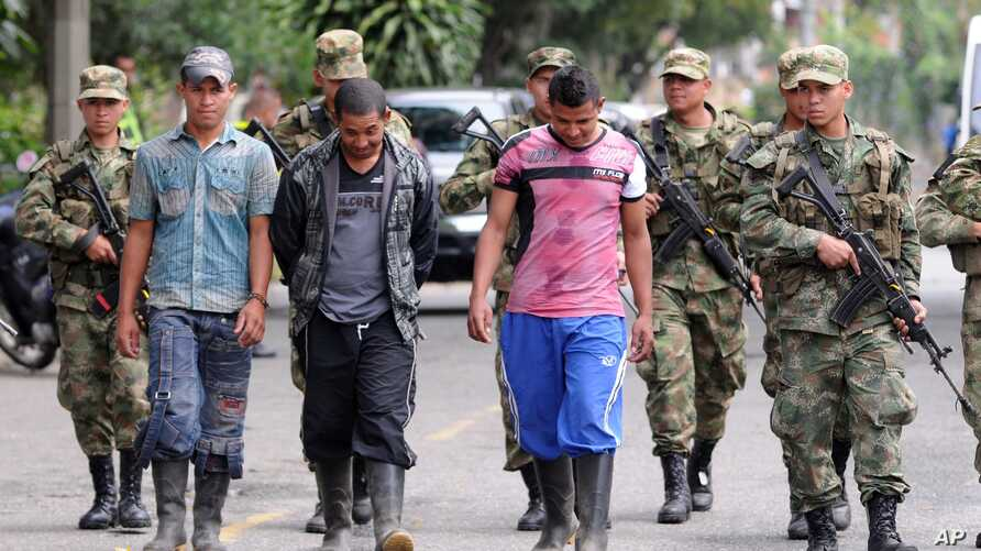 Soldiers escort three alleged rebels of the Revolutionary Armed Forces of Colombia (FARC) who allegedly surrendered to the army, in Medellin, Colombia, September 20, 2012.