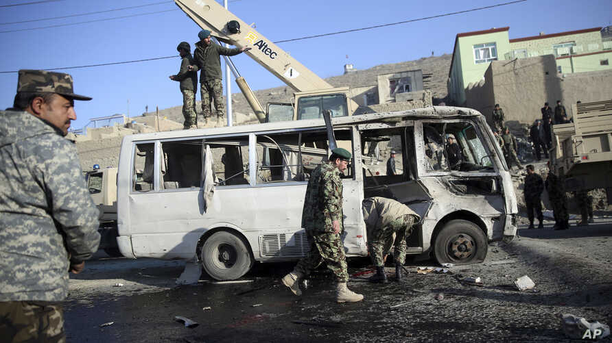 Afghan security force personnel inspect a damaged minibus at the site of a suicide attack in Kabul, Afghanistan Thursday, Dec. 11, 2014.
