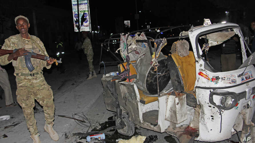 FILE - A Somali soldier stands guard near a destroyed auto rickshaw after a car bomb was detonated in Mogadishu, Somalia, Aug 4, 2017. At least three people were killed in the blast. On Aug. 10, a car bomb blast injured three people in the city.