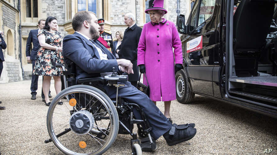 FILE - Britain's Queen Elizabeth II talks to Edward Todino as she presents him with his new 'Motability' vehicle during a ceremony at Windsor Castle, in Windsor, England, April 25, 2017.